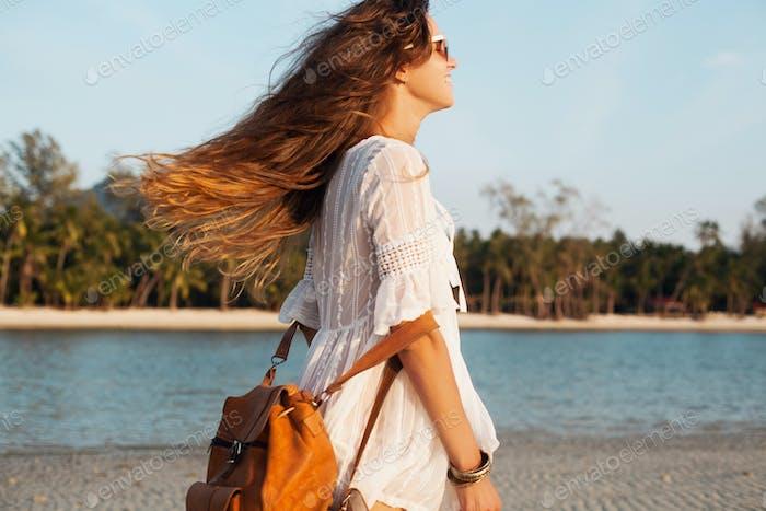 slim beautiful woman in white cotton dress walking on tropical beach