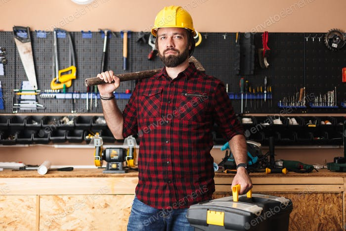 Foreman in hardhat holding hammer on shoulder and toolbox in han