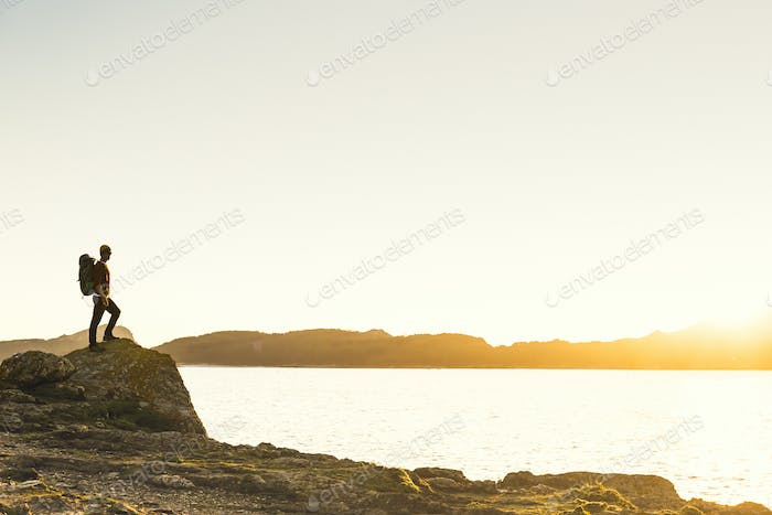 Man exploring the coast line at sunset