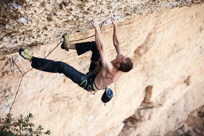 Rock climber on his challenging way up