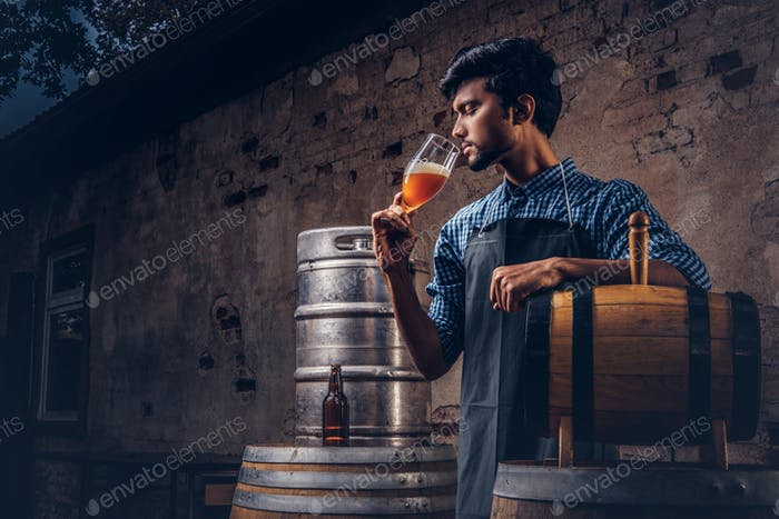 Expert brewer in apron standing near barrels checking quality of brewed drink at brewery factory.