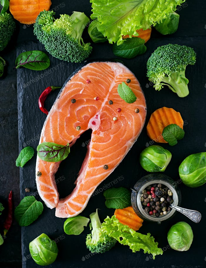 Raw salmon steak and ingredients for cooking on a dark background in a rustic style. Top view