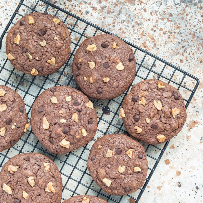 Homemade chocolate cookies with walnuts and chocolate chips on the cooling rack, top view, square