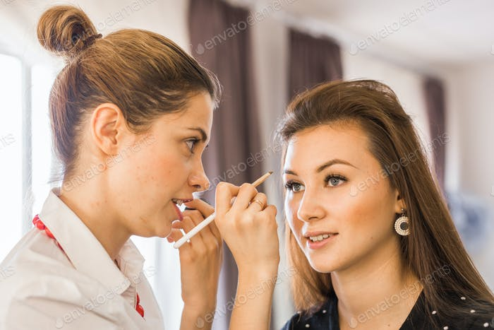 closeup portrait of beautiful woman getting professional make-up with brush.