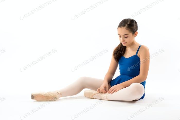 sitzende ballerina binden die schnürsenkel auf ihr schuhe