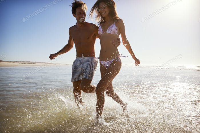 Couple Having Fun Running Through Waves On Beach Vacation