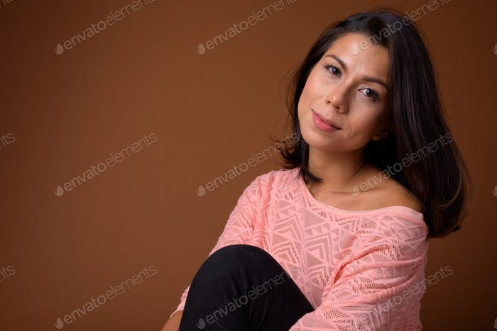 Portrait of beautiful multi ethnic woman sitting on the floor