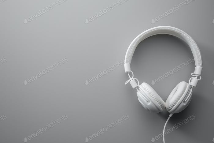 White wired stereo headphones on gray background.