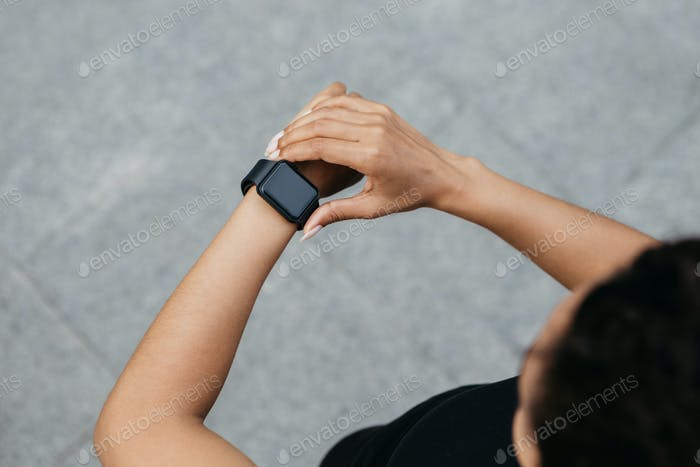 Fuera a correr. Chica afroamericana mira a reloj inteligente en la mano