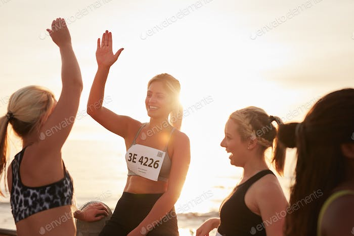Female runners high fiving each other after a race