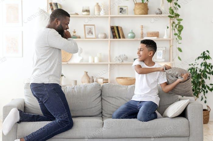 Glückliche Zeit zusammen. Schwarzer Papa Kissen Kämpfen Mit Preteen Sohn Zu Hause