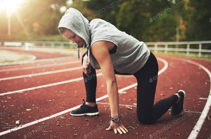 Young woman in sportswear stretching on stadium