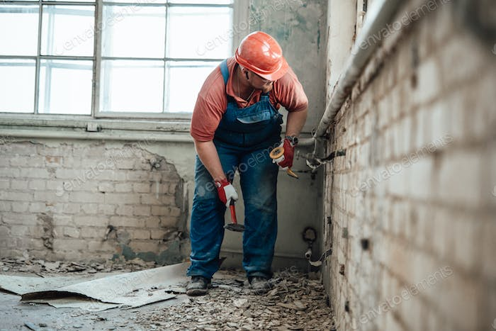 Professional builder on a construction site working on a brick wall with a hammer