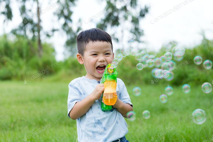 Excited little boy play with bubble gun