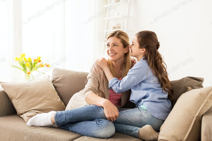 happy girl whispering secret to her mother at home