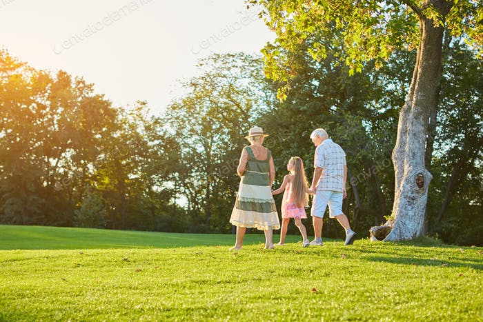 Grandparents and grandchild walking outdoors