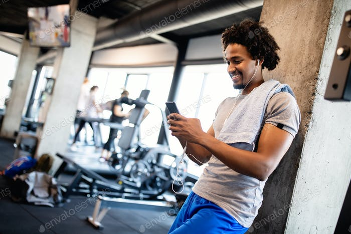 Young muscular man using mobile phone at the gym in exercise break