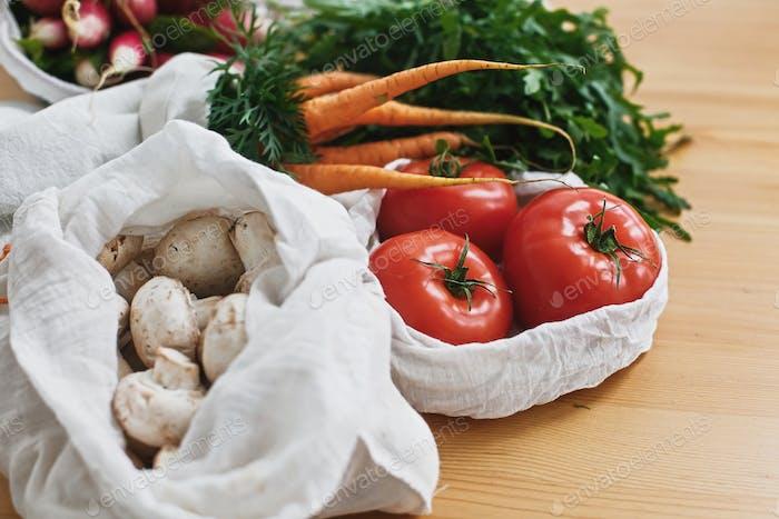Frisches Gemüse in Öko-Baumwolltüten auf Holztisch in der Küche