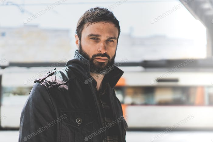 Handsome confident mature man with beard on blurred background.
