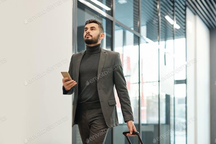 Junger Geschäftsmann in Formalwear ziehen Koffer während der Bewegung in Richtung Ausgang