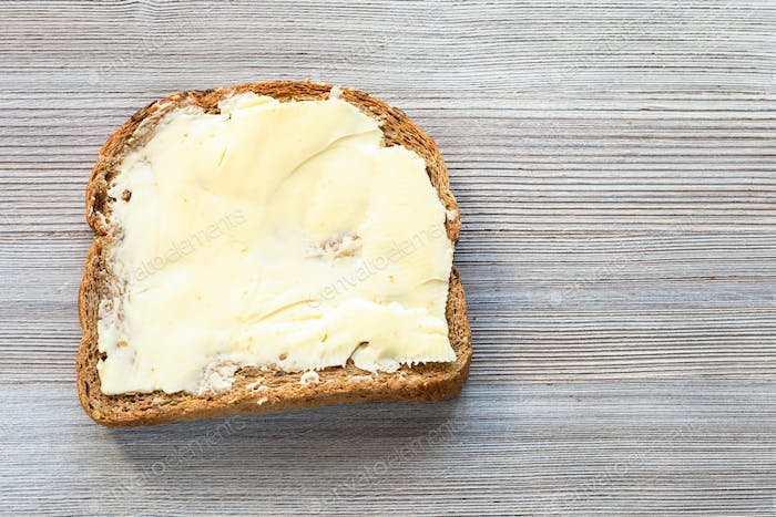 sandwich with butter on gray wooden board