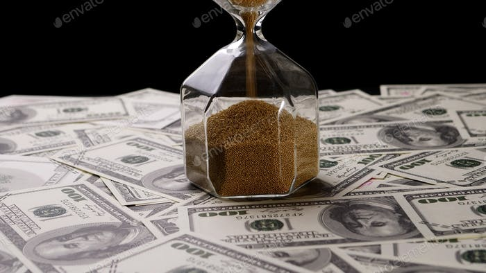 Brown sand pouring in clear sandglass on banknotes