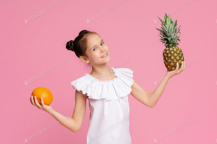 Attractive little girl holding orange and pineapple