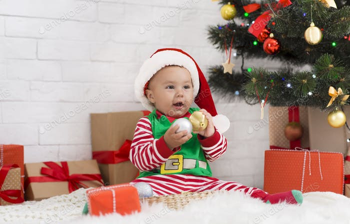 Little baby elf playing with Christmas decorations under Xmas tree
