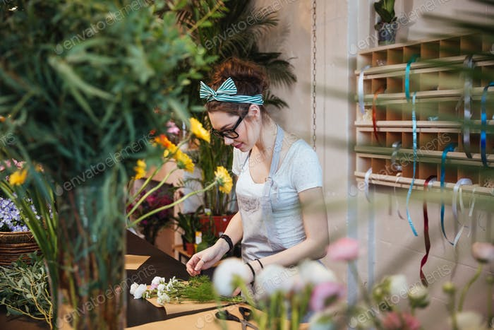 Woman florist making bouquet and working in flower shop
