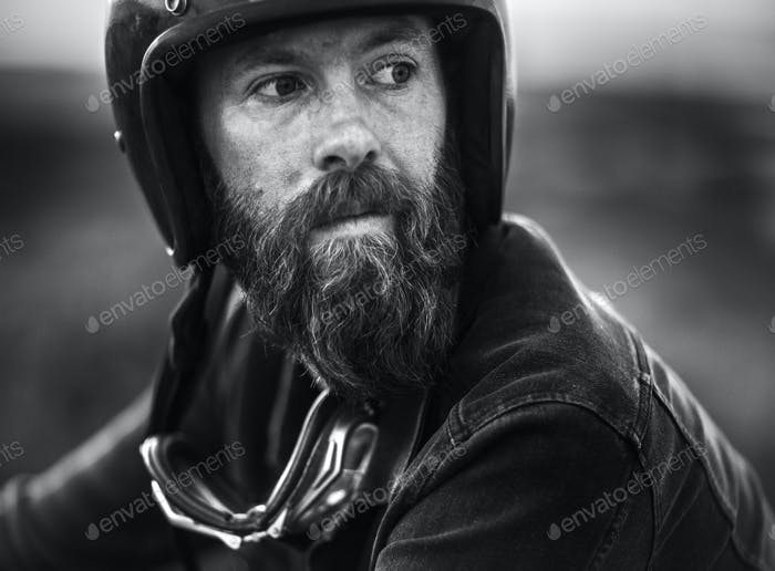 Portrait of bearded man wearing open face crash helmet, goggles round his neck.