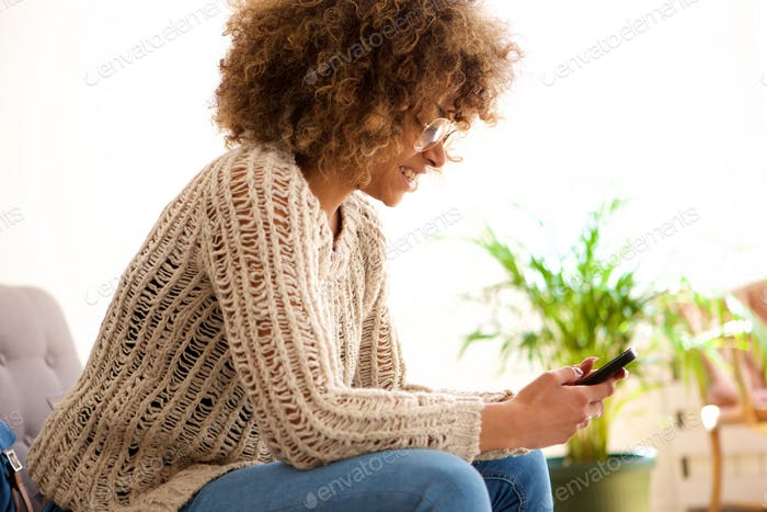 smiling young black woman sitting on sofa looking at mobile phone