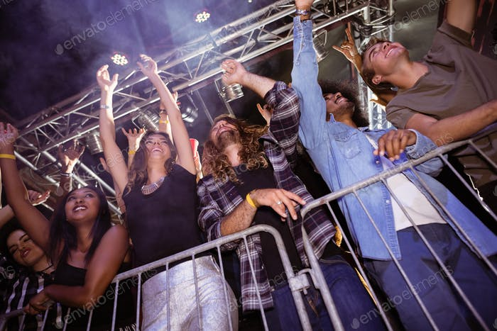 Low angle view of fans enjoying at nightclub