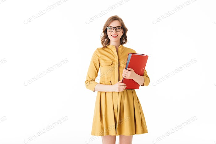 Smiling lady in eyeglasses and dress standing with red folder in hand and joyfully looking in camera