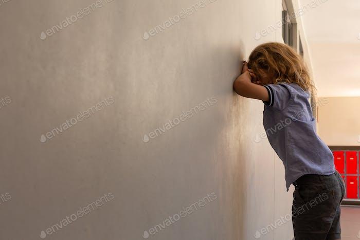 Side view of mixed -race sad schoolgirl leaning against wall in school corridor