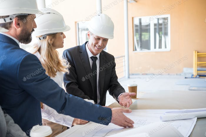 mature contractors in formal wear working with blueprints at construction