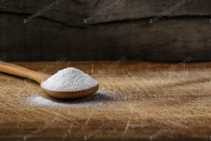 One bamboo spoon filled with white sugar