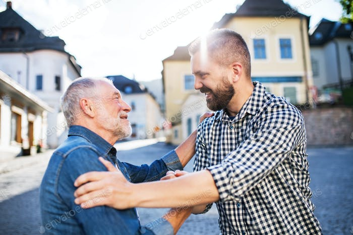 An adult hipster son with senior father on a walk in town, greeting.