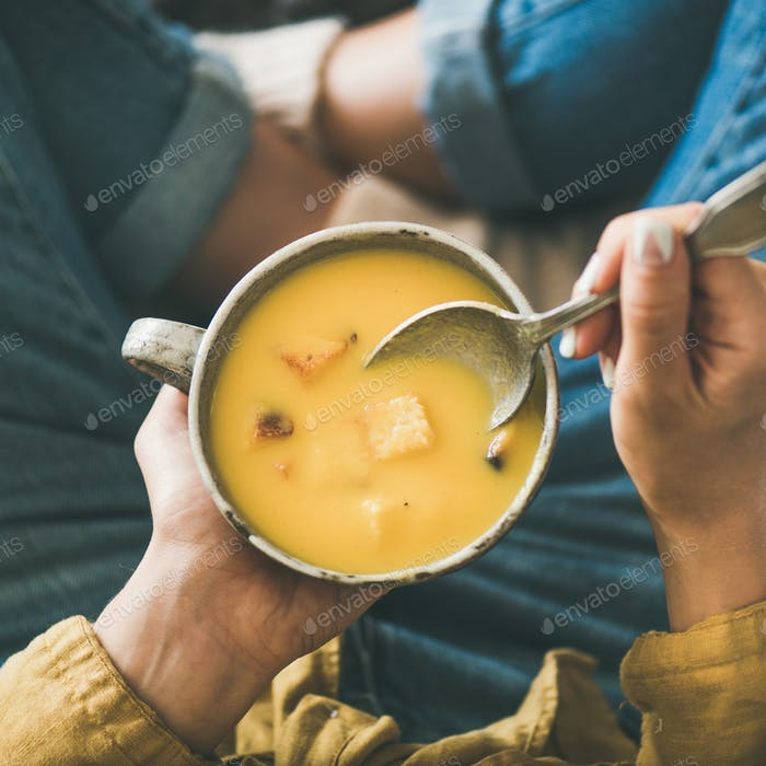 Female keeping mug of warming pumpkin cream soup, square crop