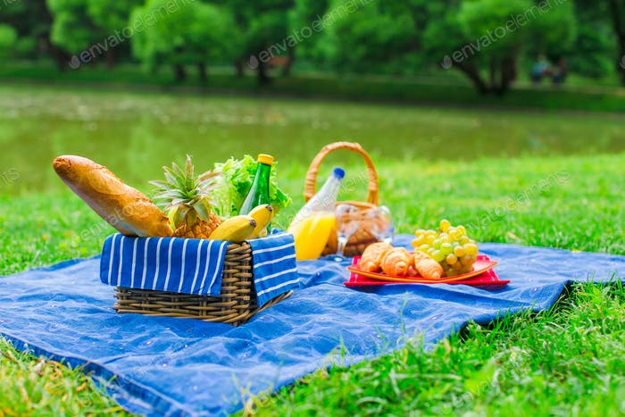 Picnic setting with white wine, pears, fruits, bread