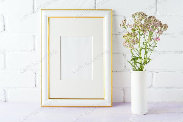 Gold decorated frame mockup with pink flowers in cylinder vase