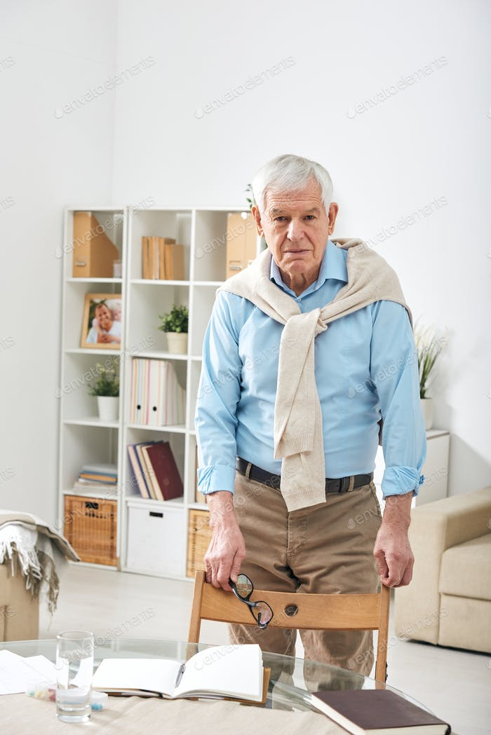 Senior retired man in casualwear looking at you while standing by chair