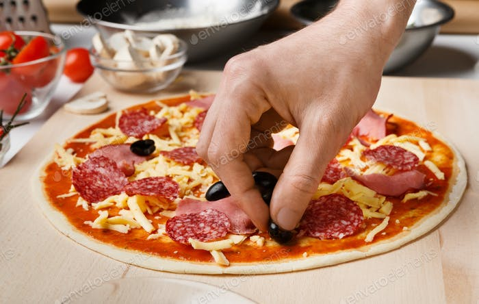 Pizzaiolo adding black olives to pizza, decorating it