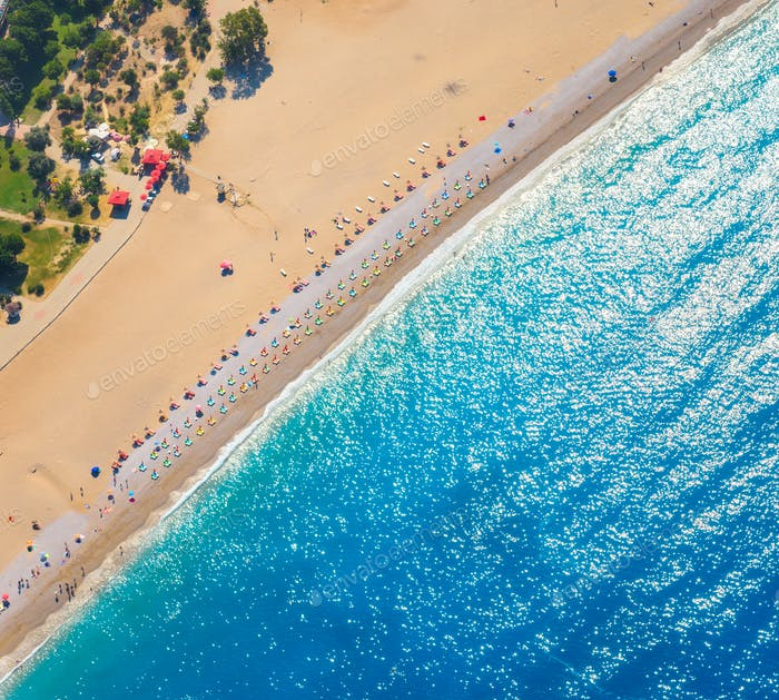 Aerial view of sandy beach with colorful chaise-lounges and blue sea