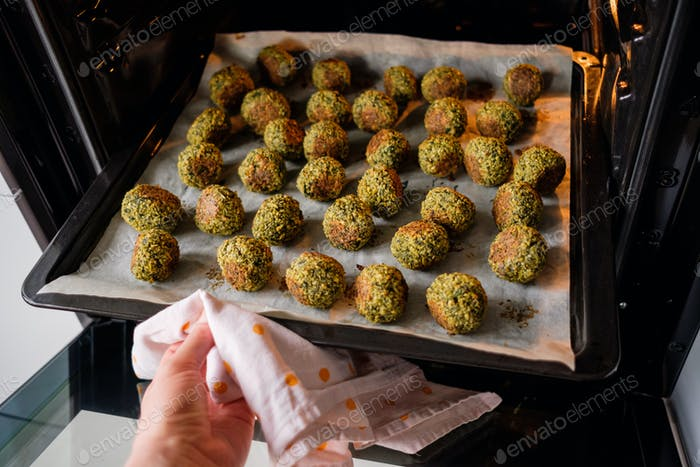 Woman hand takes the baked falafel out of the oven