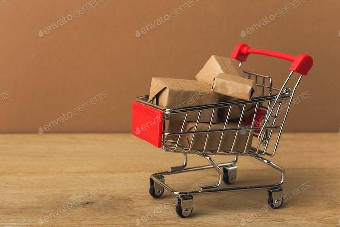 Miniatur-Einkaufswagen und Pakete auf braunem Hintergrund,