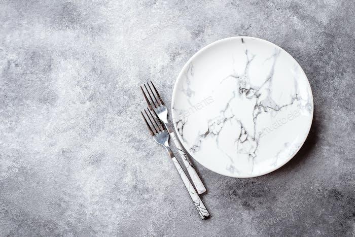 Empty ceramic marble plate on gray stone concrete table background. Copy space. Menu Recipe Concept