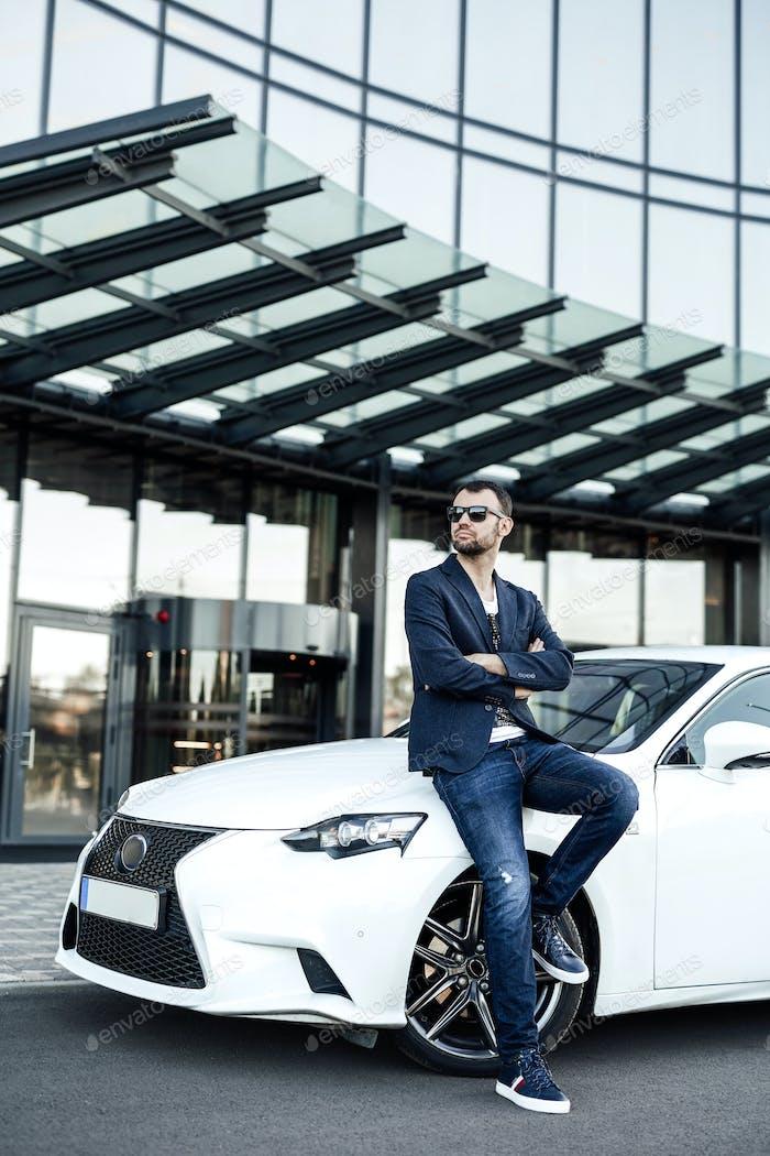 Ein Wolkenkratzer auf dem Hintergrund und selbstbewusster Kerl mit seinem Auto