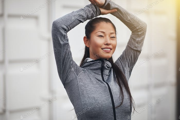 Sporty Asian woman smiling and stretching before exercising