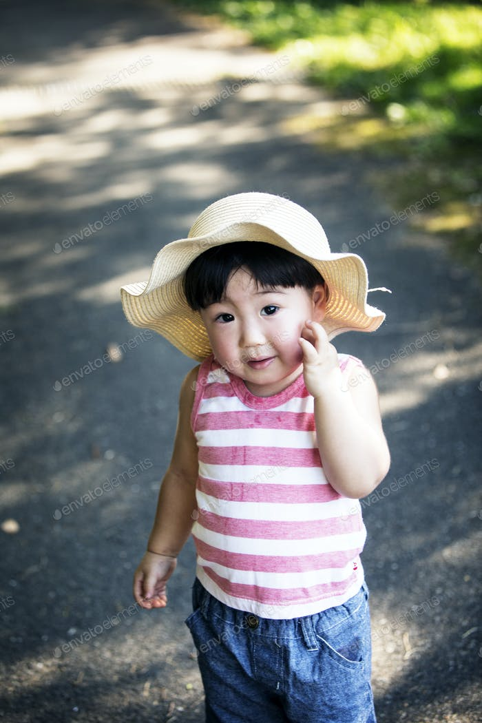 Portrait of young Japanese girl wearing sun hat, striped shirt and jeans smiling at camera.