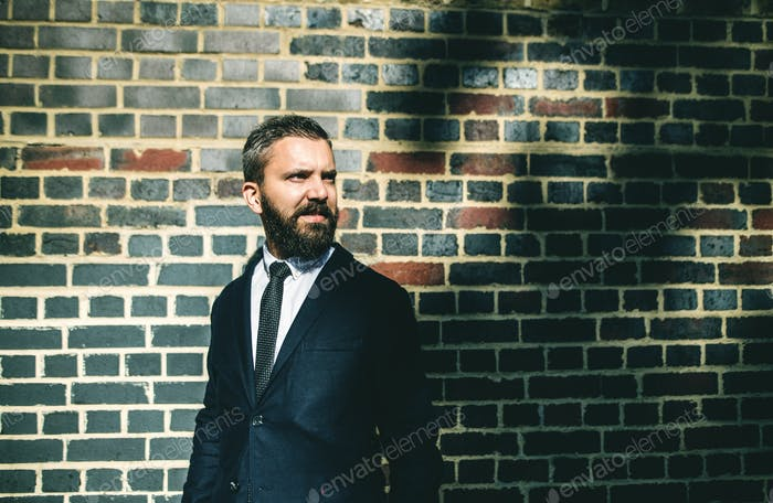 Hipster businessman standing against brick wall on the street in London.